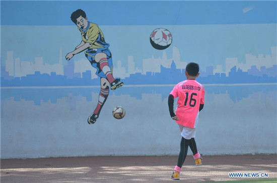 Pupils take part in football training in elementary school in Qingdao